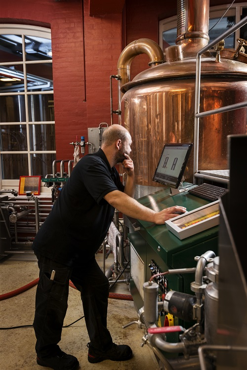 Man at his computer in a beer brewing lab